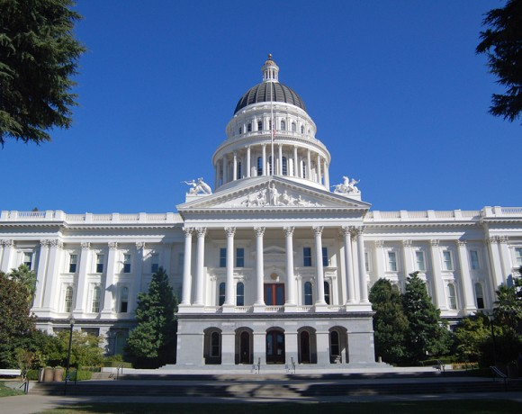 the california state capitol building in sacramento, flag flying at half mast.